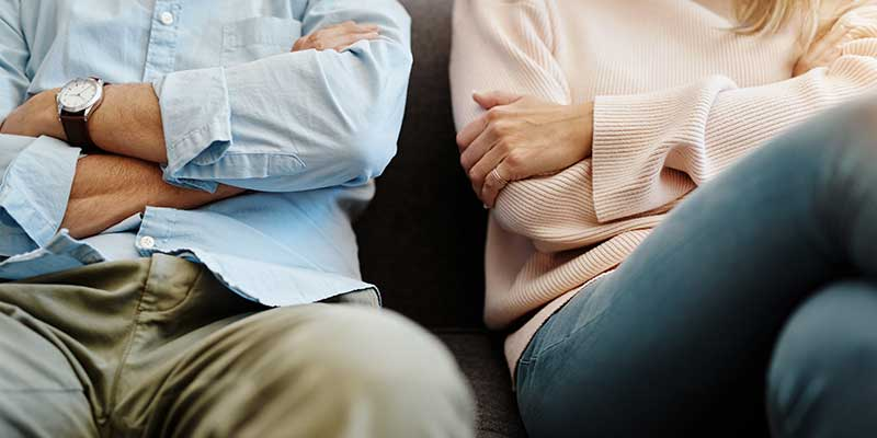Couple sitting next to each other with arms crossed