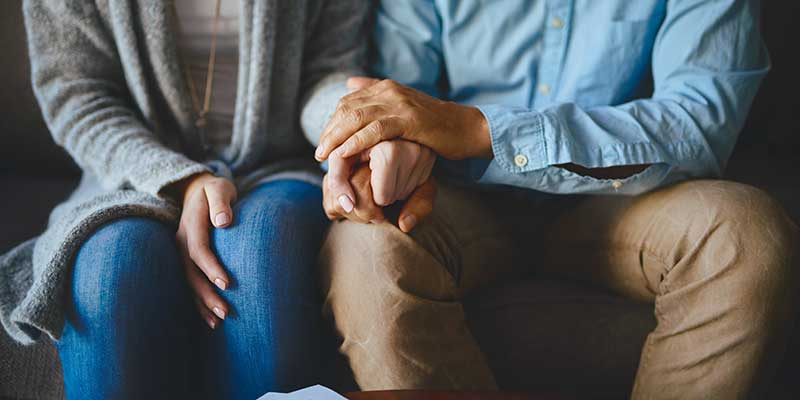 Couple holding hands sitting on couch